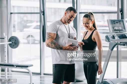 smiling young sportswoman pointing by finger on schedule on digital tablet in personal trainer hands at gym : Stock Photo