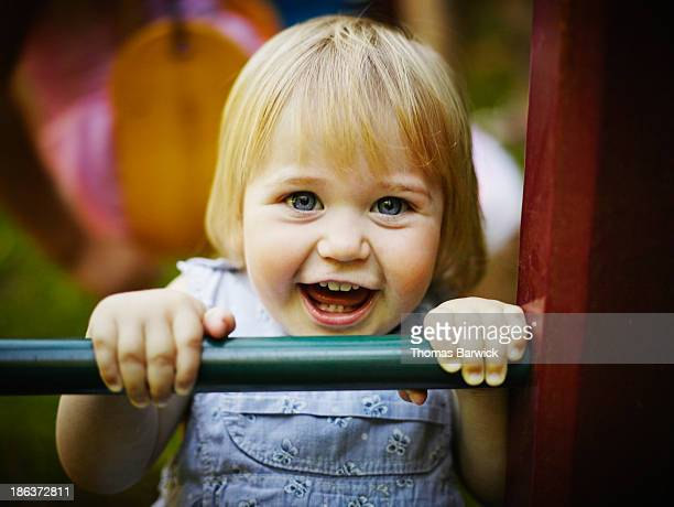 Smiling young toddler holding onto bar of playset