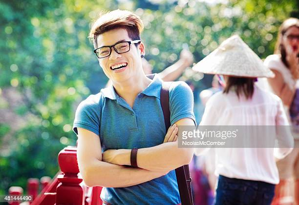Smiling young Vietnamese tourist laughing arms crossed visiting Hanoi
