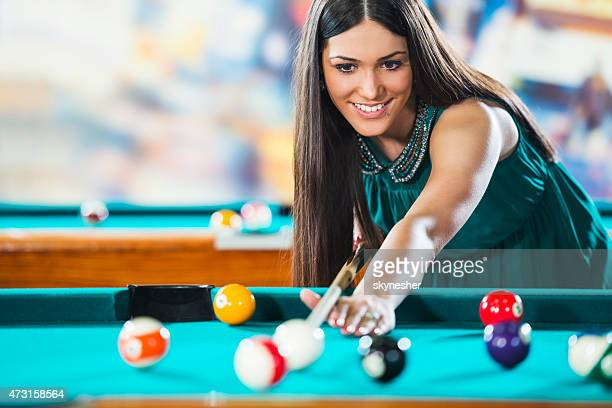 Smiling young woman aiming at pool ball and playing snooker.