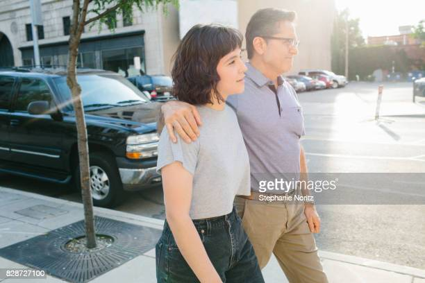 Smiling young woman and father walking together on downtown street