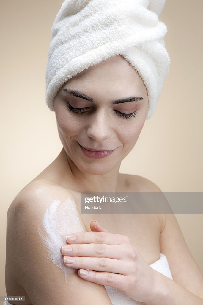 A smiling young woman applying lotion to her skin