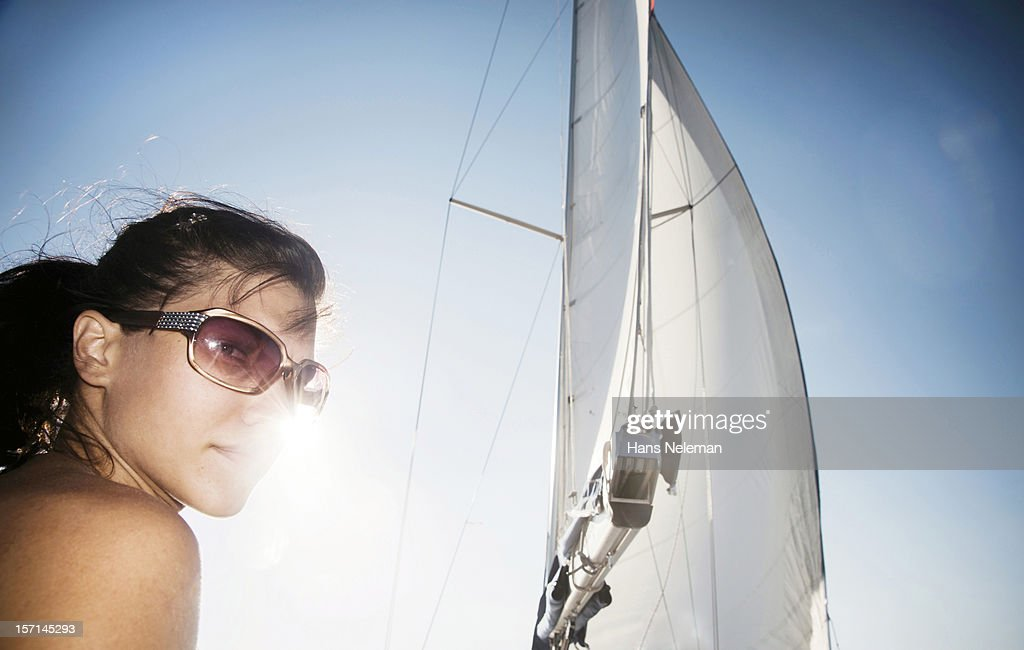 Smiling young woman by sailboat : Stock Photo