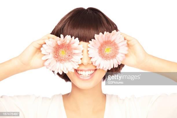 Lächelnde junge Frau, die Ihre Augen mit Blumen