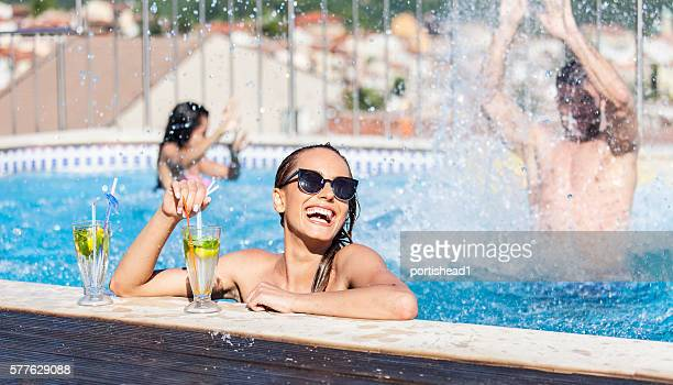 Smiling young woman drinking cocktails at swimming pool