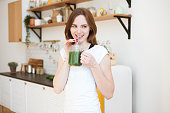 Smiling young woman drinking green smoothie juice in kitchen. Healthy Lifestyle.