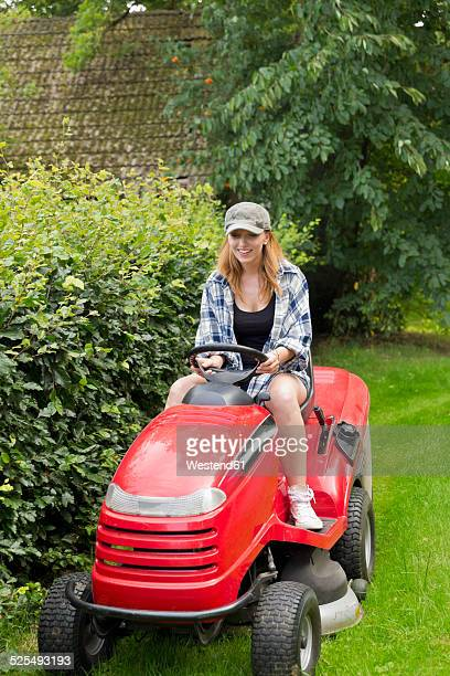 Smiling young woman driving on a lawn-mower