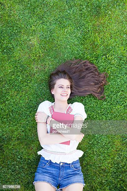 Smiling young woman embracing a book