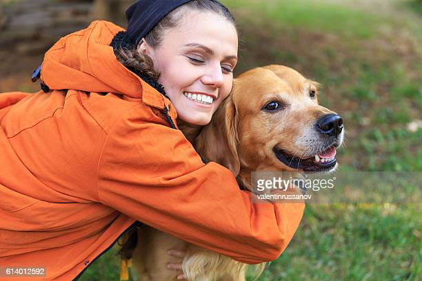Smiling young woman embracing a dog