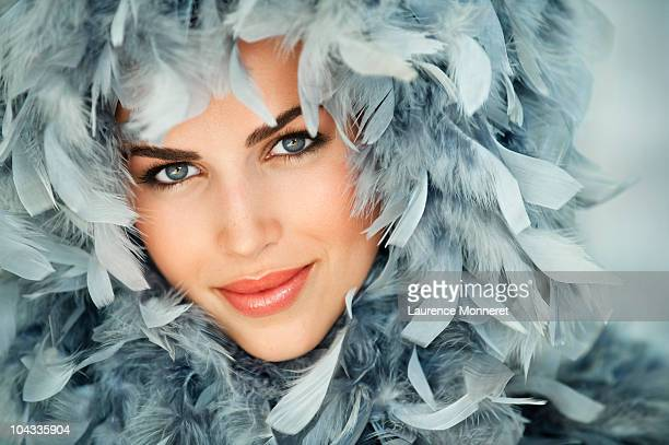 Smiling young woman framed by blue feathers