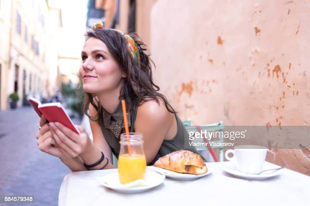 Smiling young woman having breakfast outdors in Rome