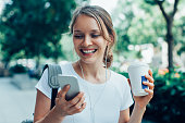 Closeup portrait of smiling young beautiful woman walking, holding drink, wearing headphones and having video call on smartphone on street