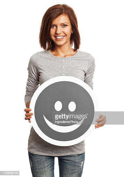 Smiling young woman holding happy smile sign isolated on white.