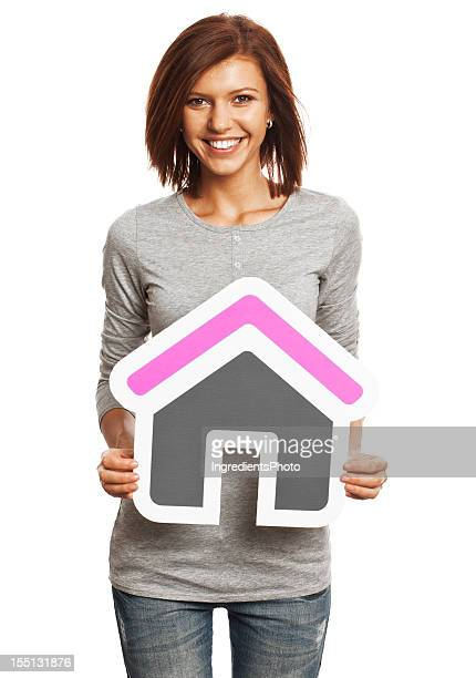 Smiling young woman holding house sign isolated on white background