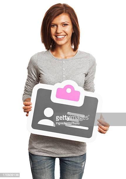 Sorridente giovane donna con scheda di identificazione segno isolato su bianco.