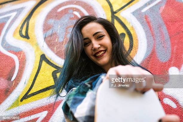 Smiling young woman holding longboard