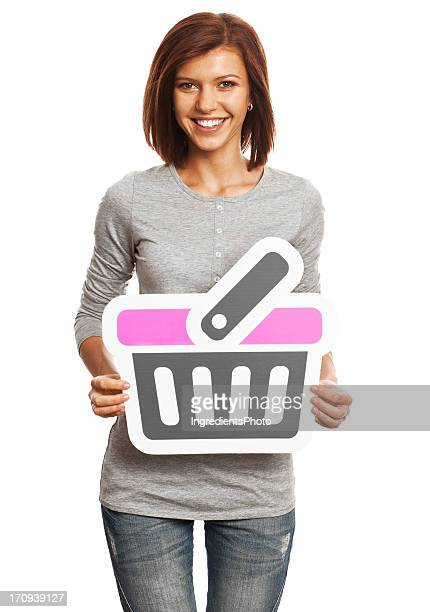 Smiling young woman holding shopping cart sign isolated on white.
