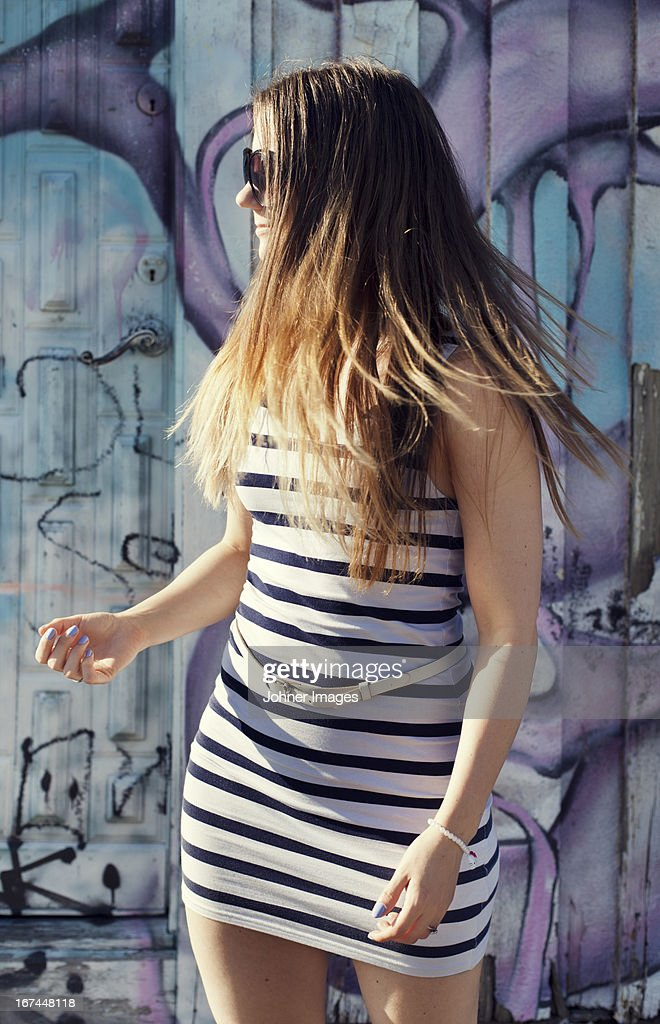 Smiling young woman in mini dress looking away : Stock Photo