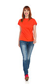 Young woman in orange shirt, jeans and red sneakers is walking towards camera and smiling. Full length studio shot isolated on white.