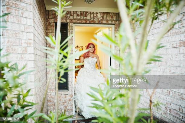 Smiling young woman in quinceanera gown walking out front door of home