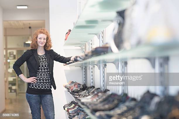 Smiling young woman in shoe shop
