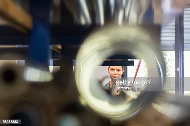 Smiling young woman in workshop behind tube