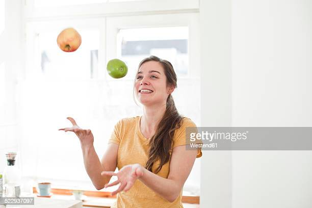 Smiling young woman juggling with two apples in her kitchen