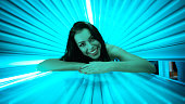 Smiling young woman laying on solarium, tanning skin treatment
