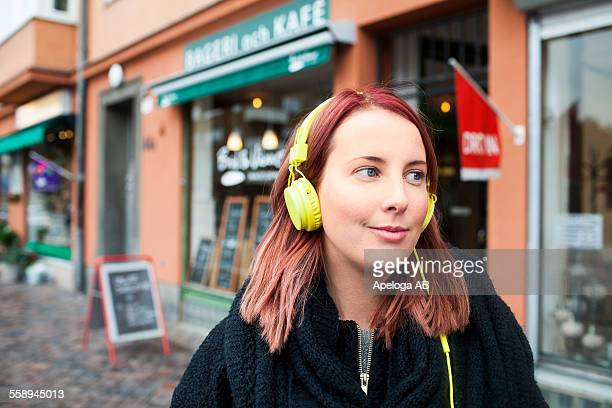 Smiling young woman listening music through headphones outside cafeteria