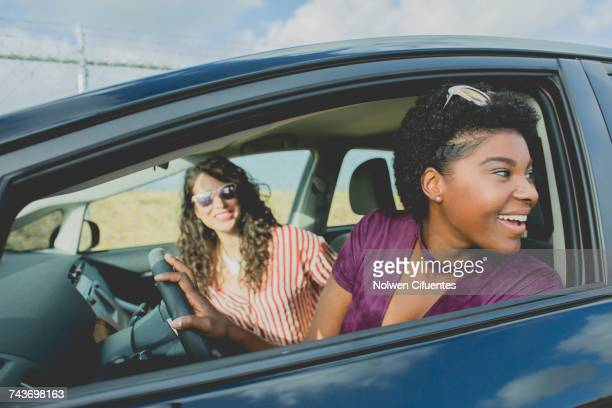 Smiling young woman looking away while sitting with female friend in car