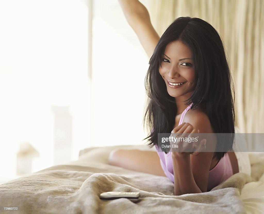 Smiling young woman lying on bed, beckoning to camera