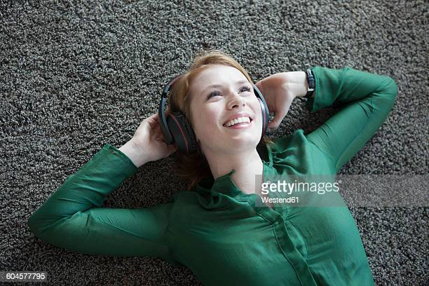 Smiling young woman lying on carpet hearing music with headphones