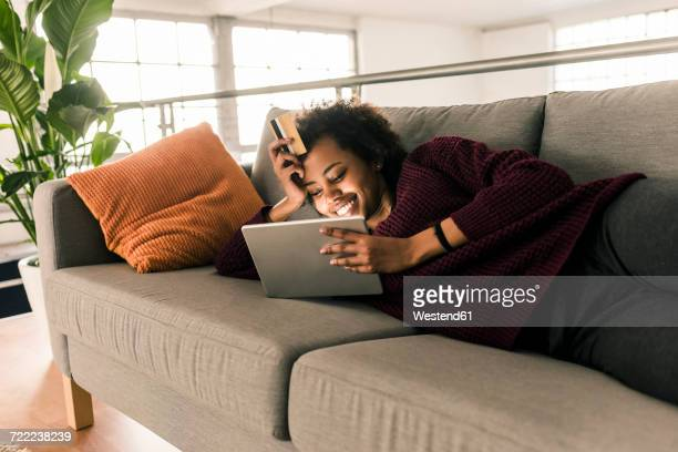 Smiling young woman lying on couch holding credit card and tablet