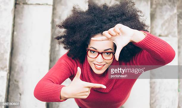 Smiling young woman making frame with fingers on stairs