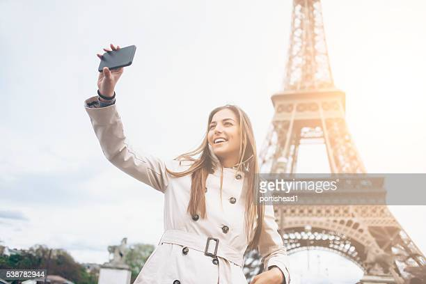 Smiling young woman making selfie in front of Eiffel tower