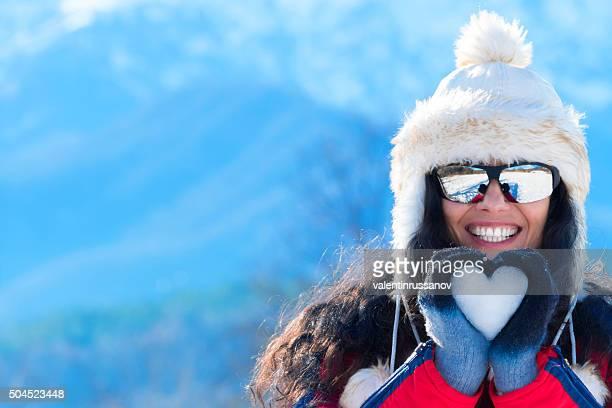Sonriente mujer joven haciendo corazón de nieve en invierno de la montaña