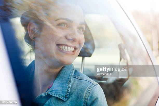 Smiling young woman on back seat of a car
