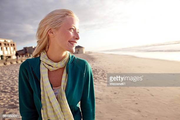 Smiling young woman on beach at sunrise