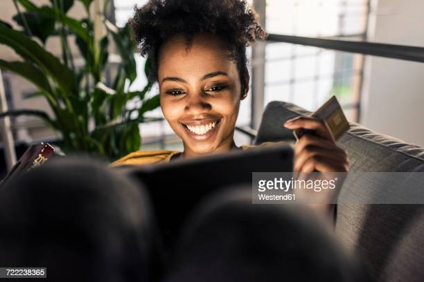 Smiling young woman on couch with credit card and laptop