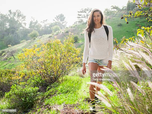 Smiling young woman on hiking trail