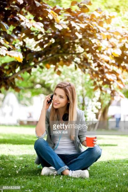 Lächelnde junge Frau oder Teenager-Mädchen am Smartphone sprechen