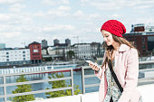 Smiling young woman outdoors looking at cell phone