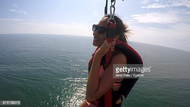 Smiling Young Woman Parasailing Over Sea Against Sky