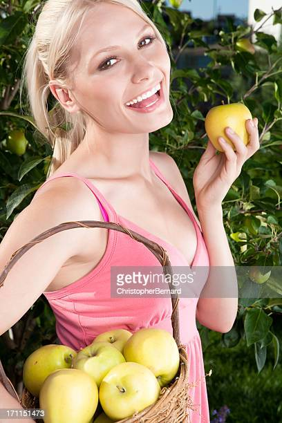 Smiling young woman picking apples