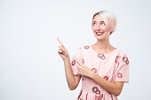 Smiling young woman pointing finger away isolated on a grey background. Look here, you can not miss this sale