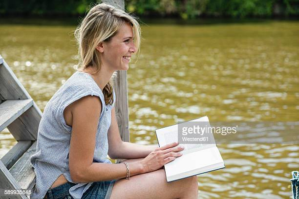 Smiling young woman reading book at the waterfront