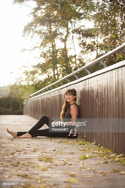 Smiling young woman relaxing on a footbridge