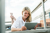 Smiling young woman relaxing on deck using digital tablet