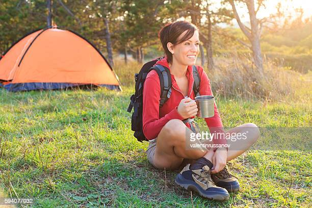 Smiling young woman resting in front of a tent