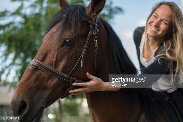 Smiling young woman riding stroking horse